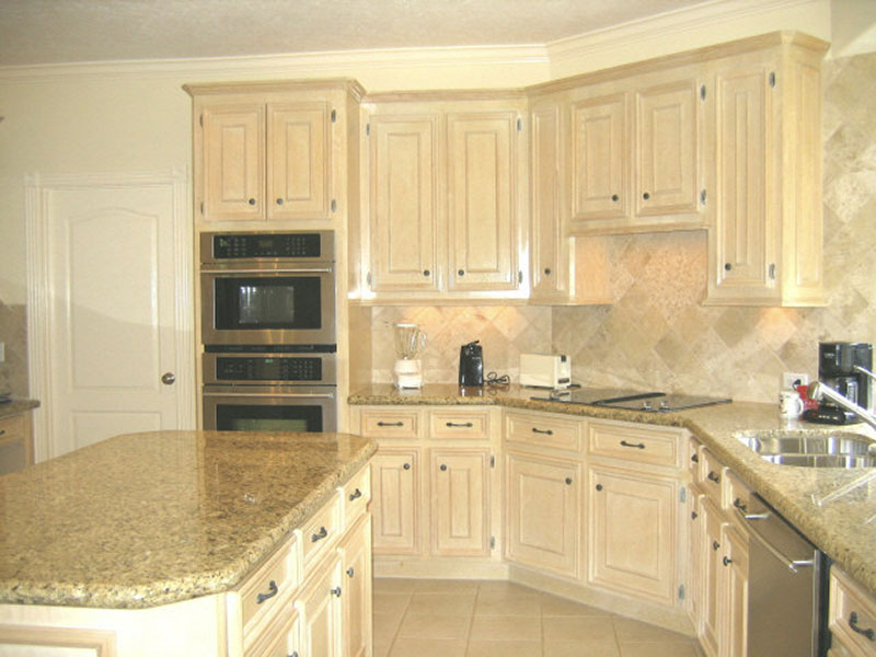 Oak kitchen that was refinished to a custom color backsplash is clear